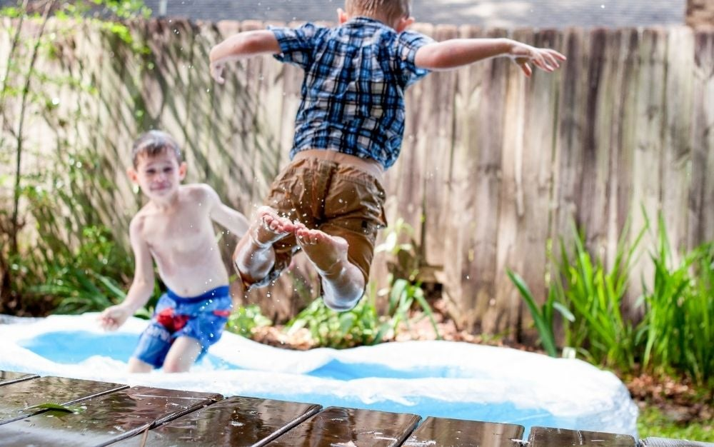 Two boys playing into a outdoor swimming pool and one of them is jumping into the pool water.