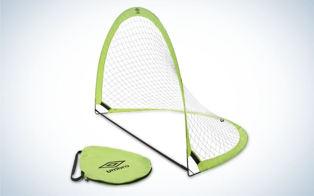 A gate to play football with a black net and green color on the side and a green bag in front of it.