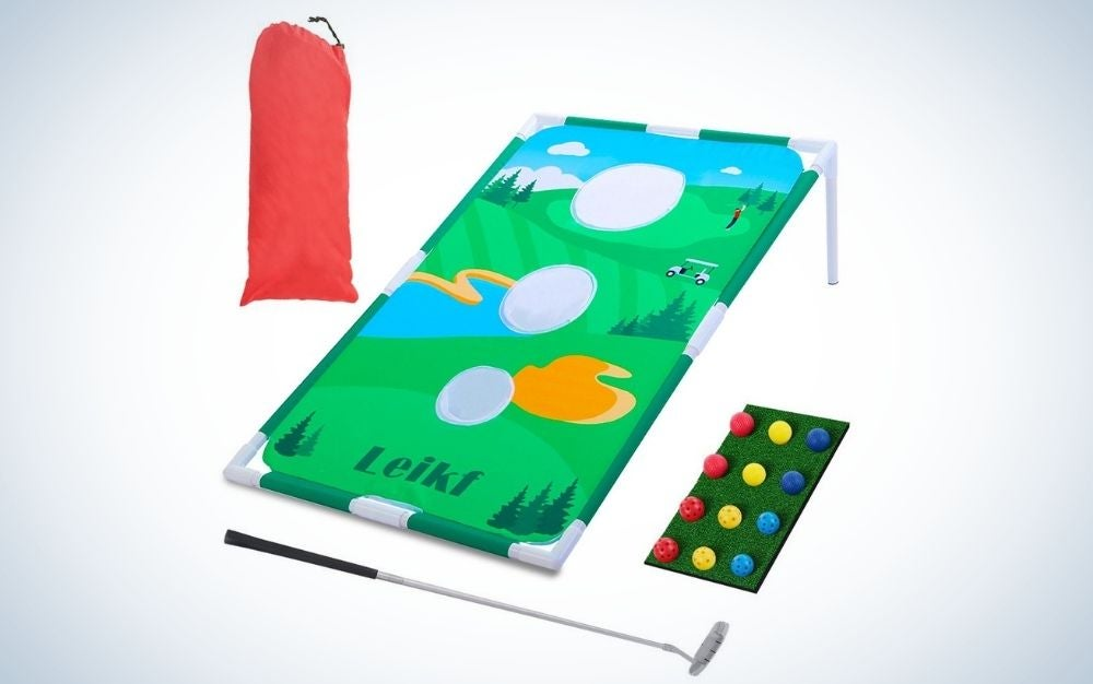 A portable golf backyard in solid green with a few holes in it, as well as a red bag and a box of golf balls and a golf club.