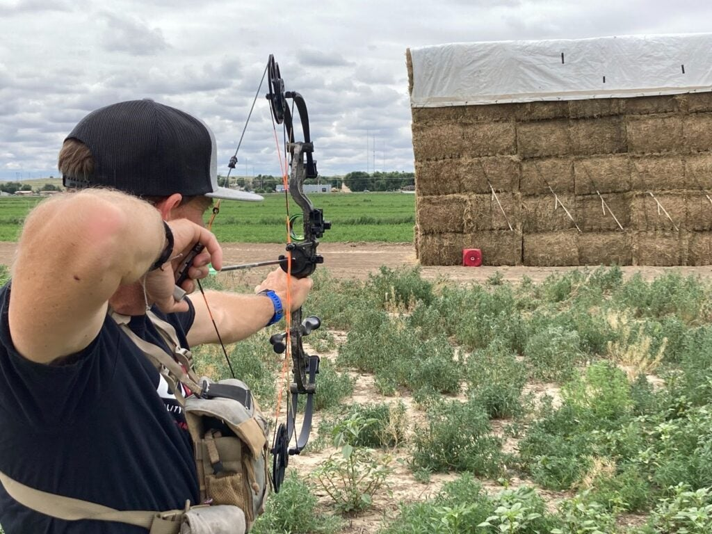 Man shooting compound bow