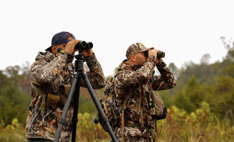 Bowhunters glassing through binoculars.