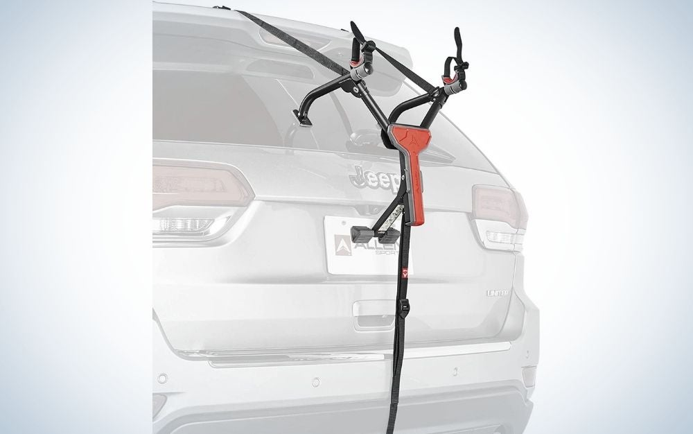 A trunk car bike carrier for bicycles, which is portable, dark gray with orange parts and is located behind a high top and gray color.
