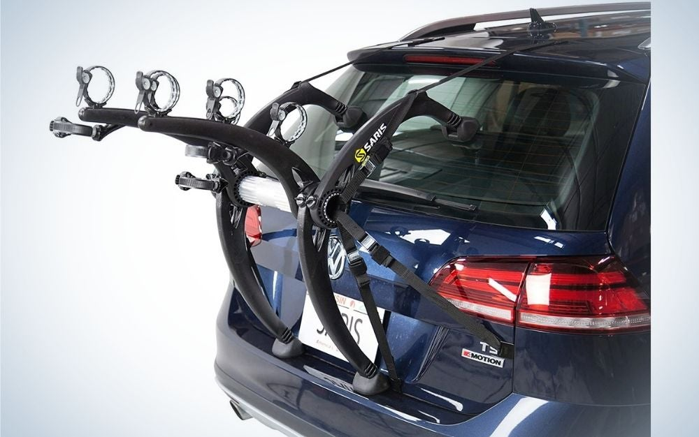 A trunk car bike carrier for three bicycles, placed behind a top and blue car.