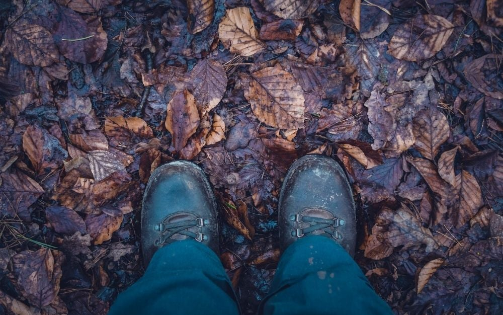 A pair of black boots of a person who treads on a ground with wet soil and leaves.