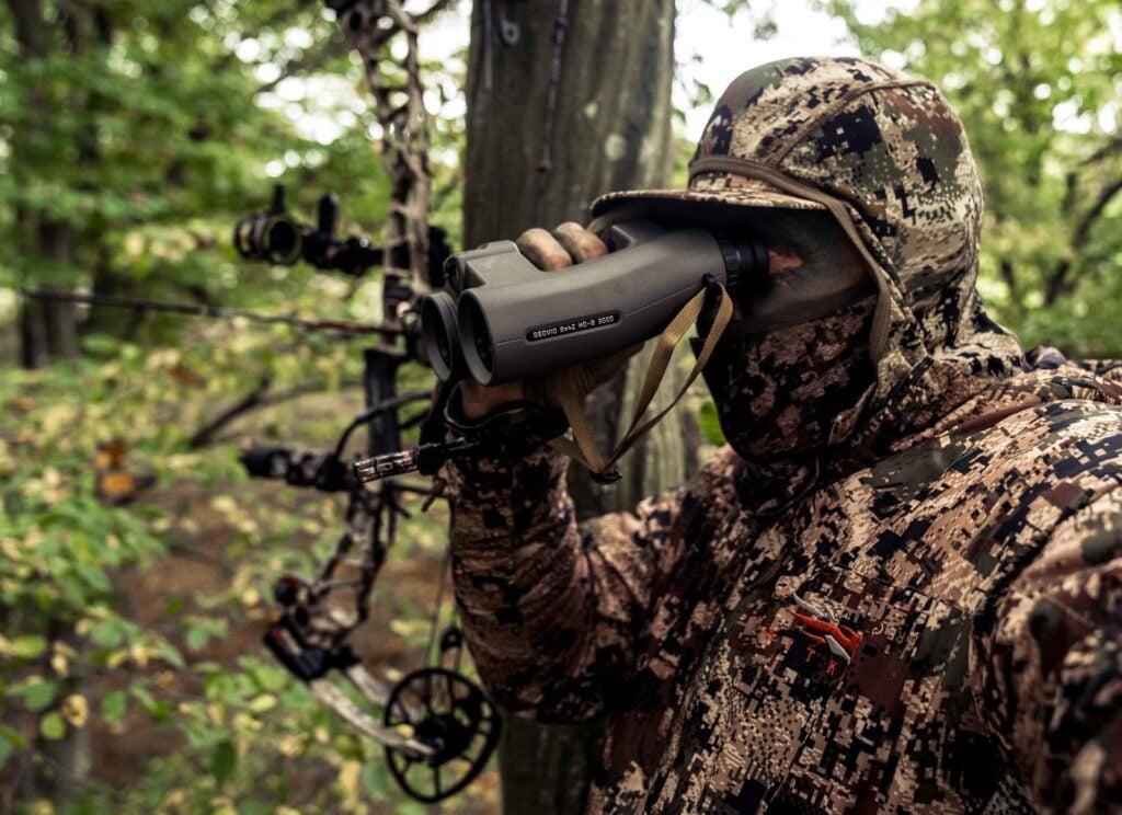 Hunter holding Leica Geovid 3200.com binoculars