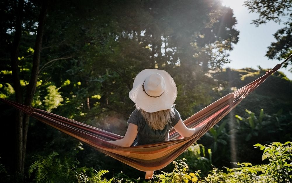 Women on a white hat sitting on a brown hammock