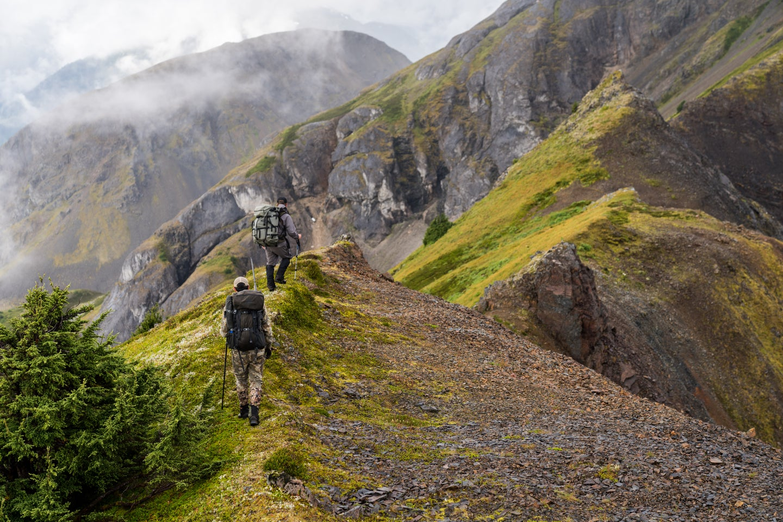 Two mountain goat hunters walk a ridge.