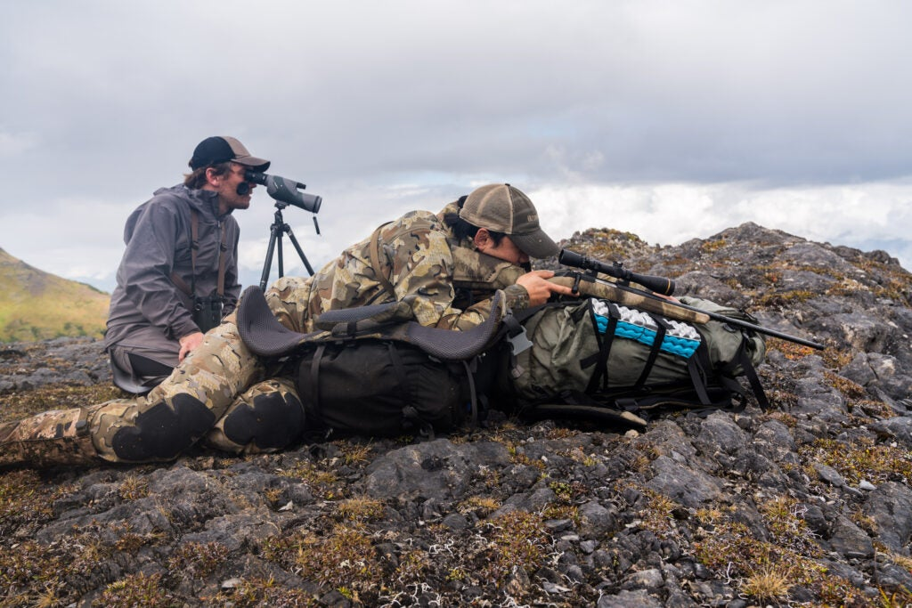 A hunter and a spotter, set up for a mountain goat hunt.