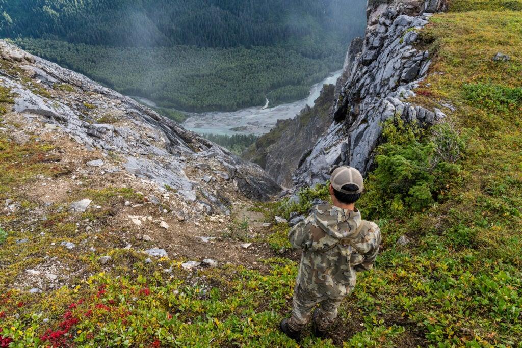 A mountain goat hunter looks down a steep chute to a fallen goat.