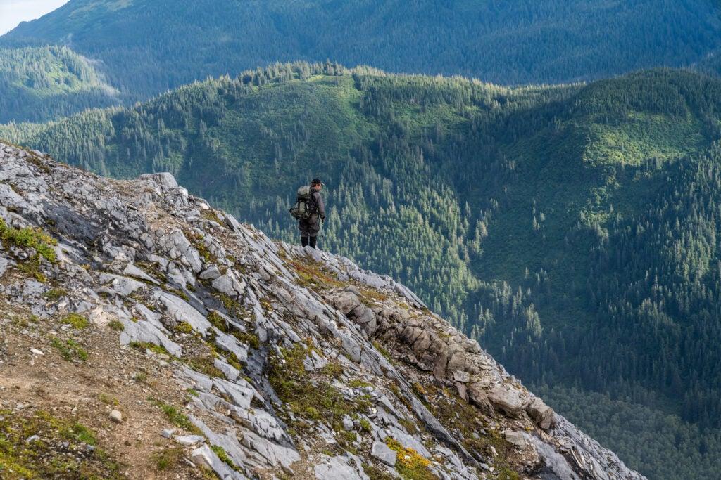 A mountain goat hunter checks a ridge