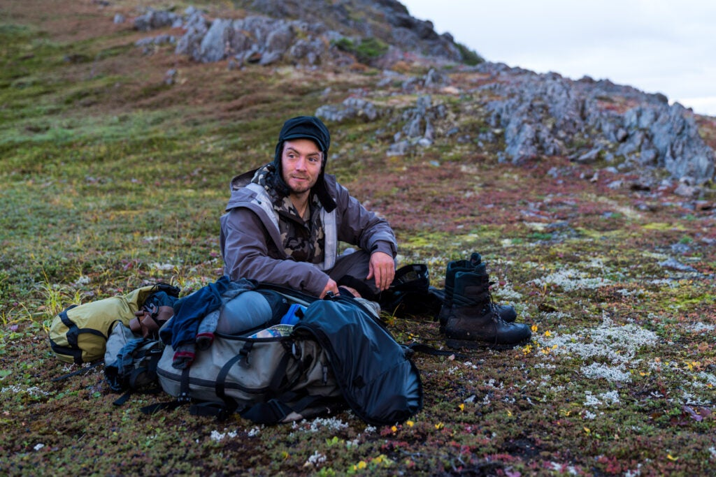 A mountain goat guide rests by his gear.