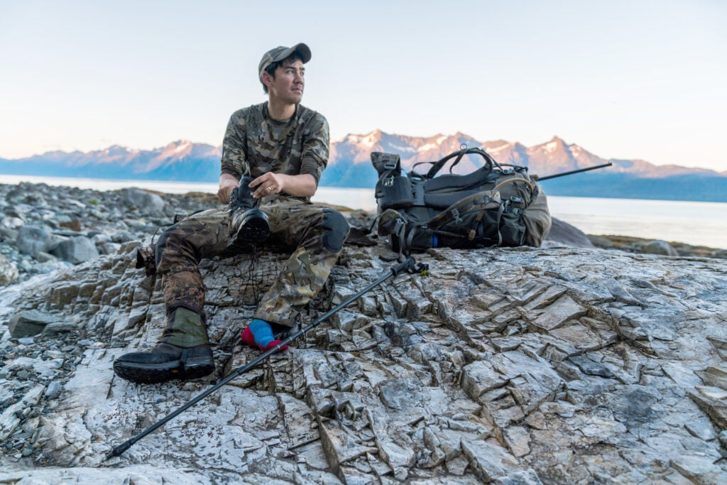 A mountain goat hunter empties rocks from his boot.