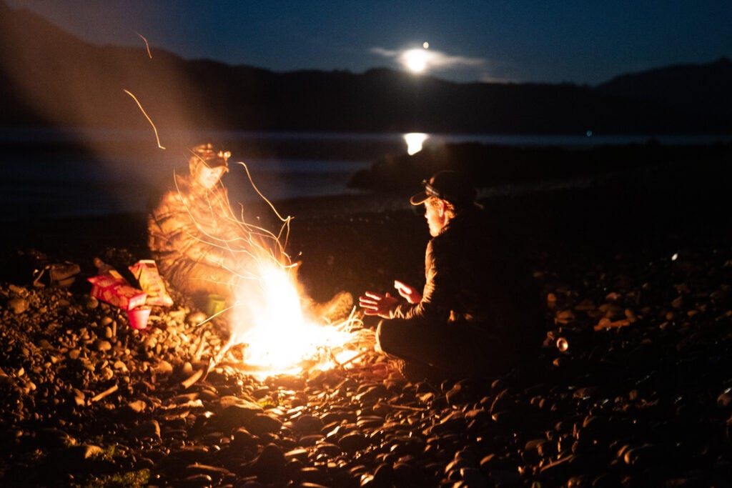 Two mountain goat hunters by a campfire in Alaska.