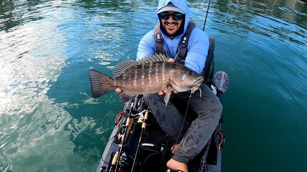 fisherman holding fish in kayak