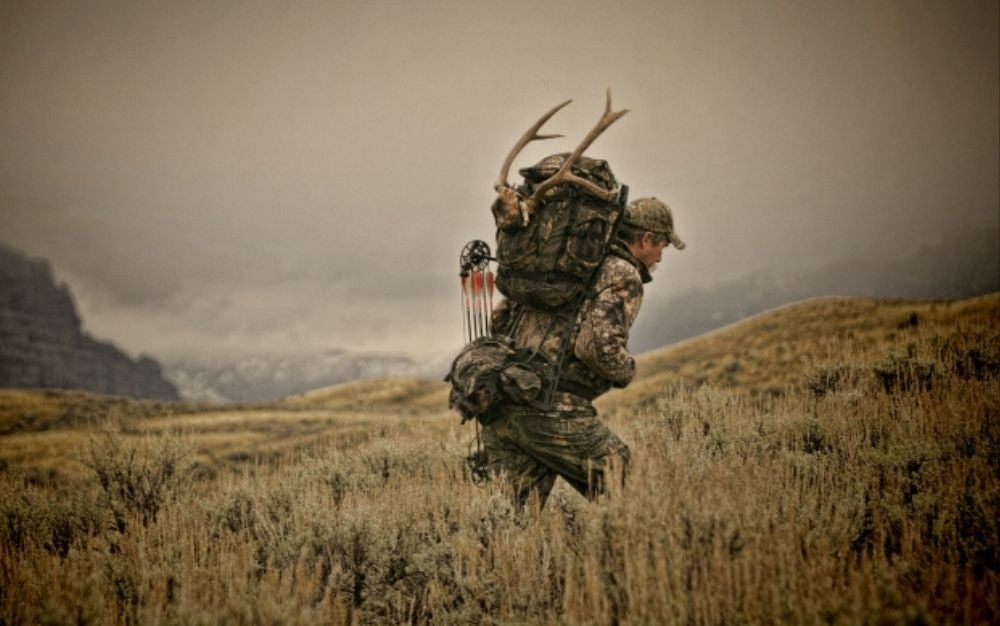 Person walking and carrying a hunting backpack