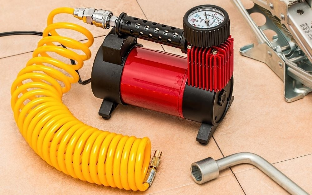 An air compressor on the ground with some beige plates and a yellow circular tube.