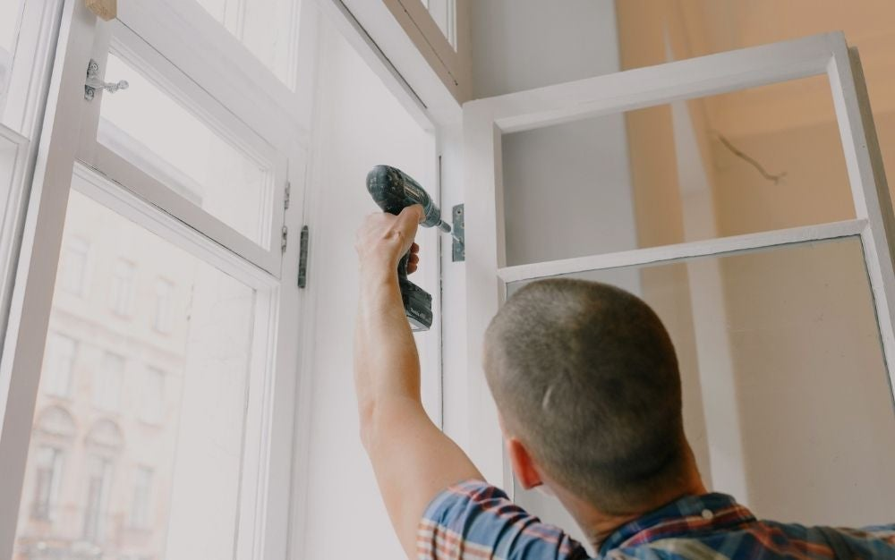 Person using a cordless screwdriver to install a window.