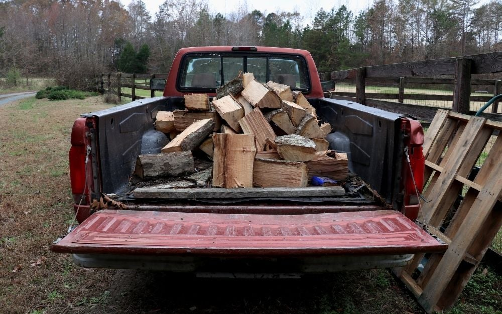 A pickup truck loaded with firewood.