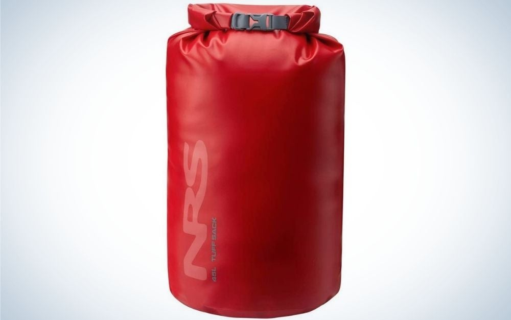 A large bag similar to a boxing bag which is red and in the shape of a cylinder.