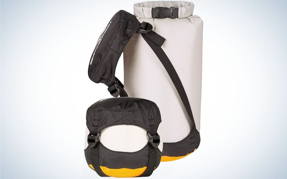 A large bag similar to a boxing bag which is white in color and in the shape of a cylinder, next to it are a waist bag with a long black belt and a small square bag of different colors.