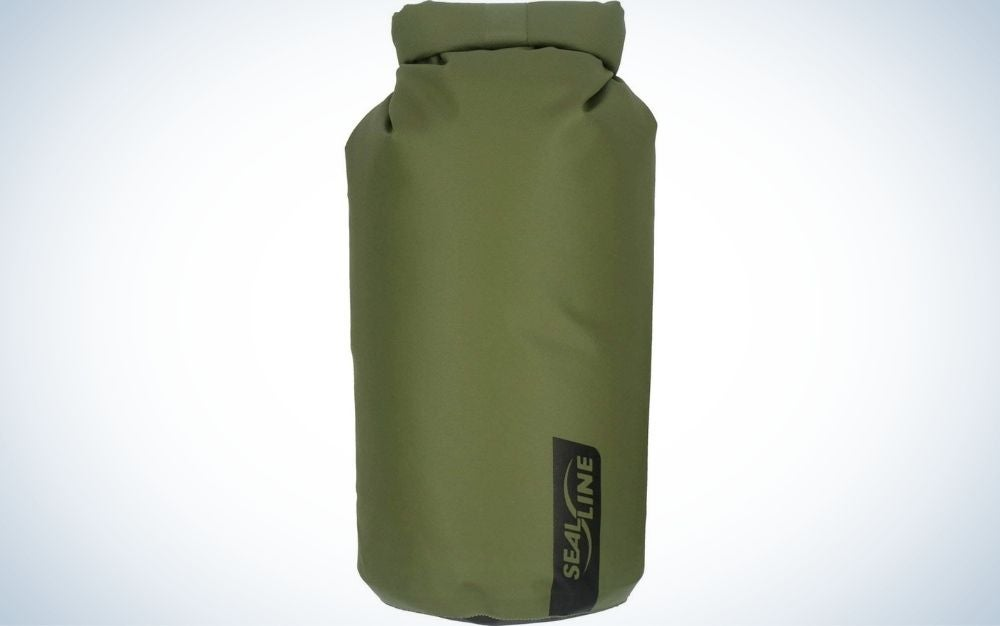 A large bag similar to a boxing bag which is green and in the shape of a cylinder.
