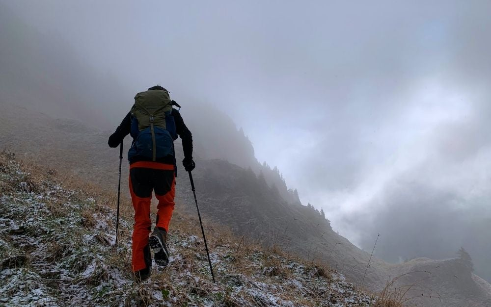 A man with dark jacket and orange climbing jeans climbing over the rocks of the mountain with two sticks of trekking poles.