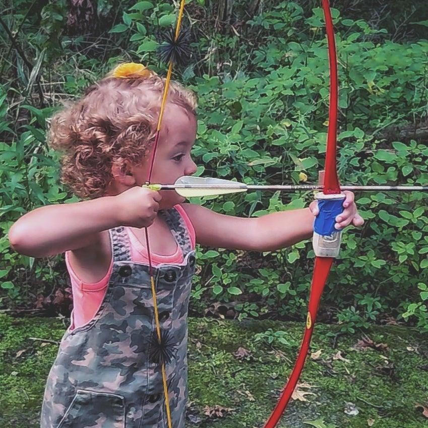 A little girl shoots a red Bear bow.