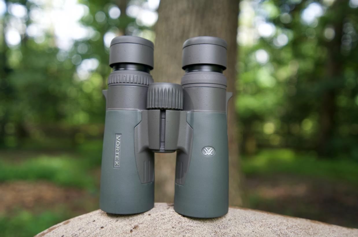 Green binoculars sitting on top of a rock