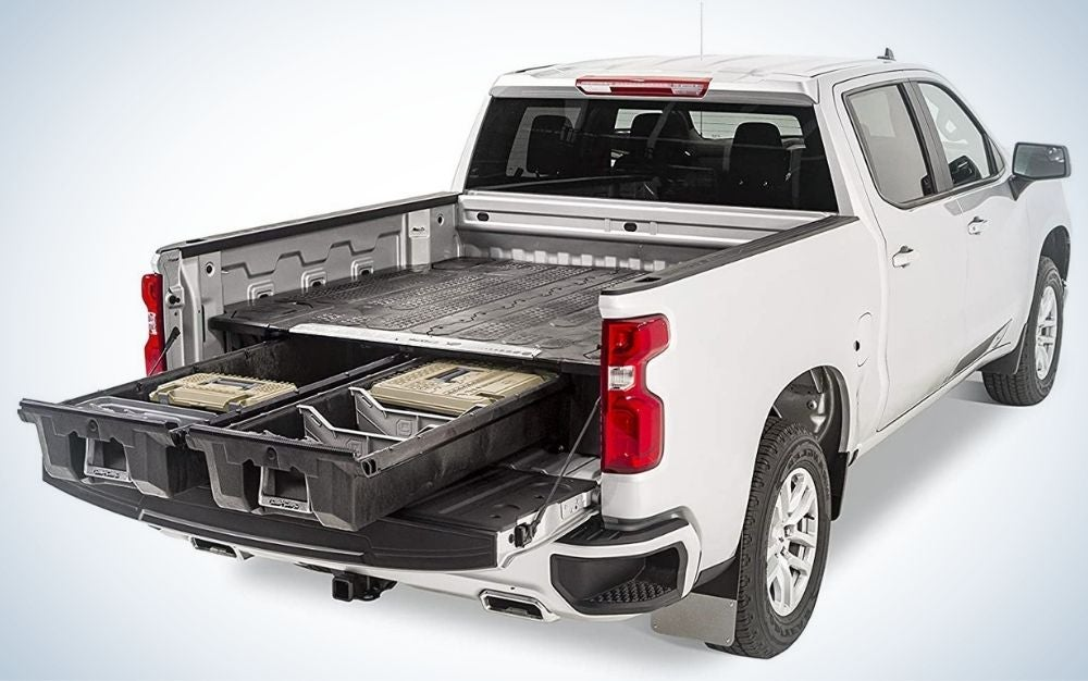 A truck which is white in color and from the back has a large space and two left heavy and complementary accessories for the car.