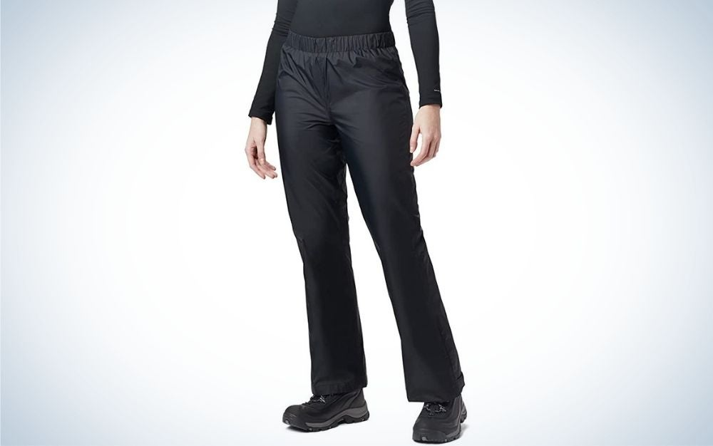 A pair of black and tight pants with little shine, which are worn by a woman in a black shirt and a pair of black sneakers as well.