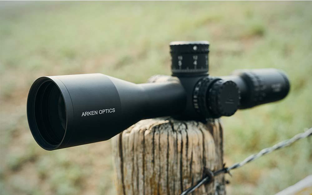 A black Arken scope sitting on a fence post