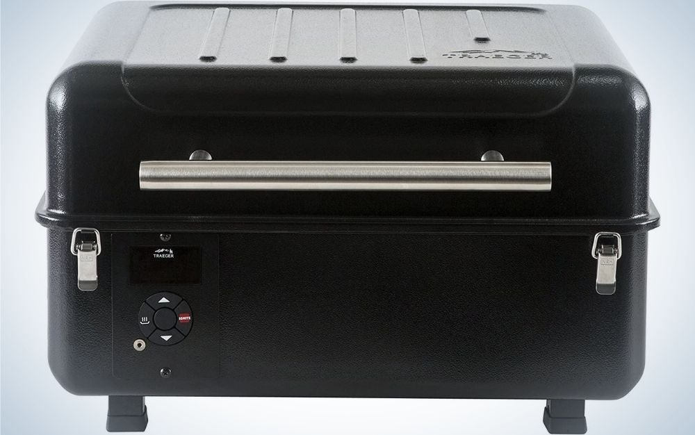 A portable grill which is in the shape of a large and wide black rectangle and has two supporting legs below it.