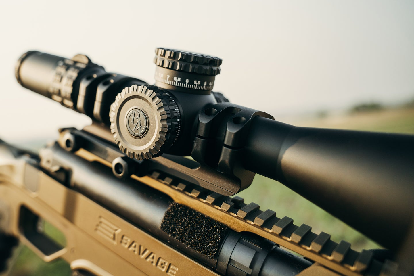 A Primary Arms scope on top of a gold rifle shot at an angle