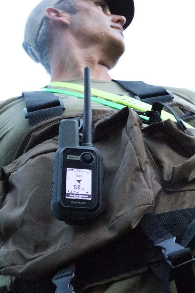 The Garmin Alpha 10 clipped to a hunter's vest