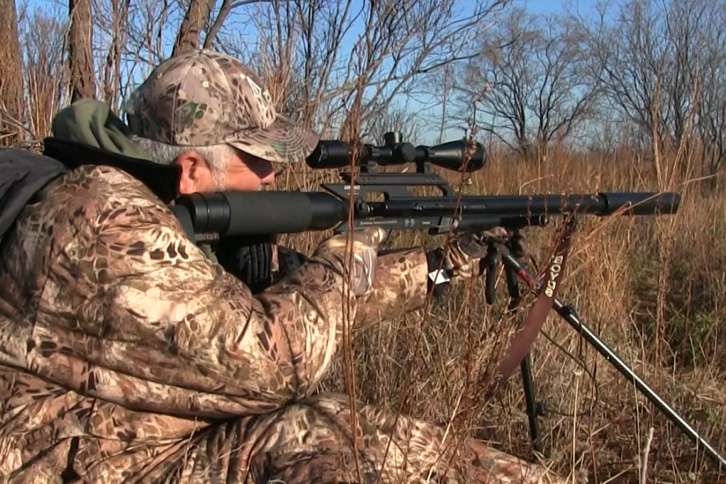 A man in camouflage aiming the AirForce Texan air rifle on a hunt