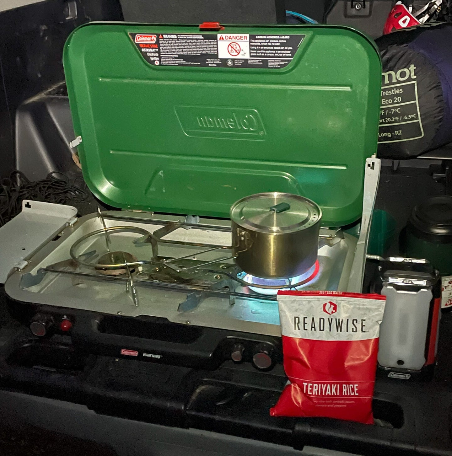 A green Coleman stove cooking a ReadyWise teriyaki meal