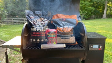 A variety of wood pellet bags sitting on a grill