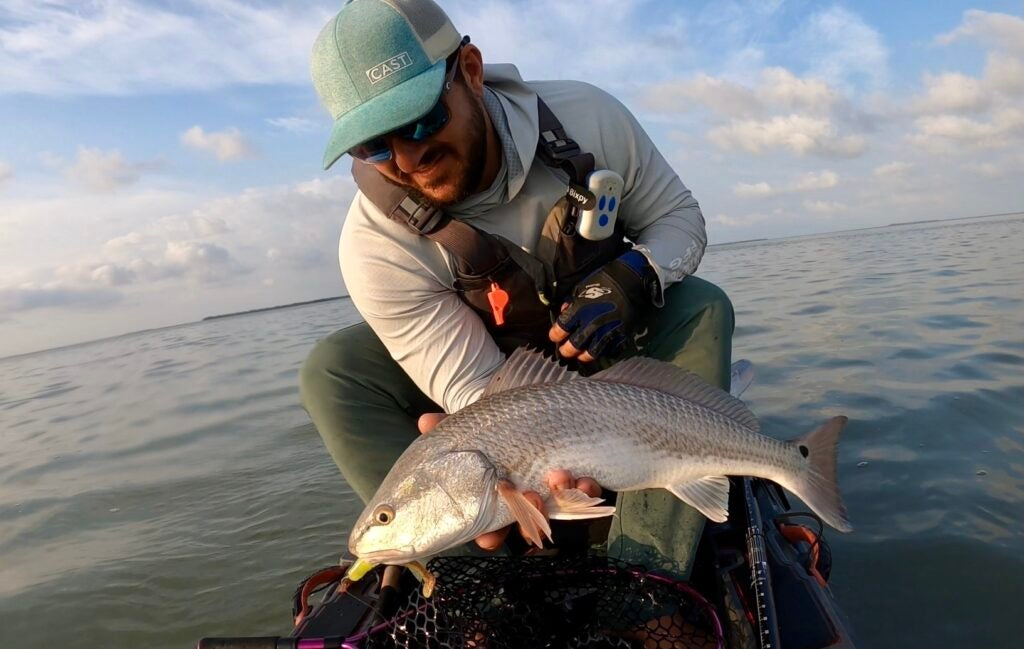 A man holds a redfish on the water