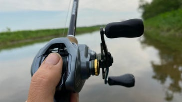An angler's thumb on a baitcasting reel over a body of water