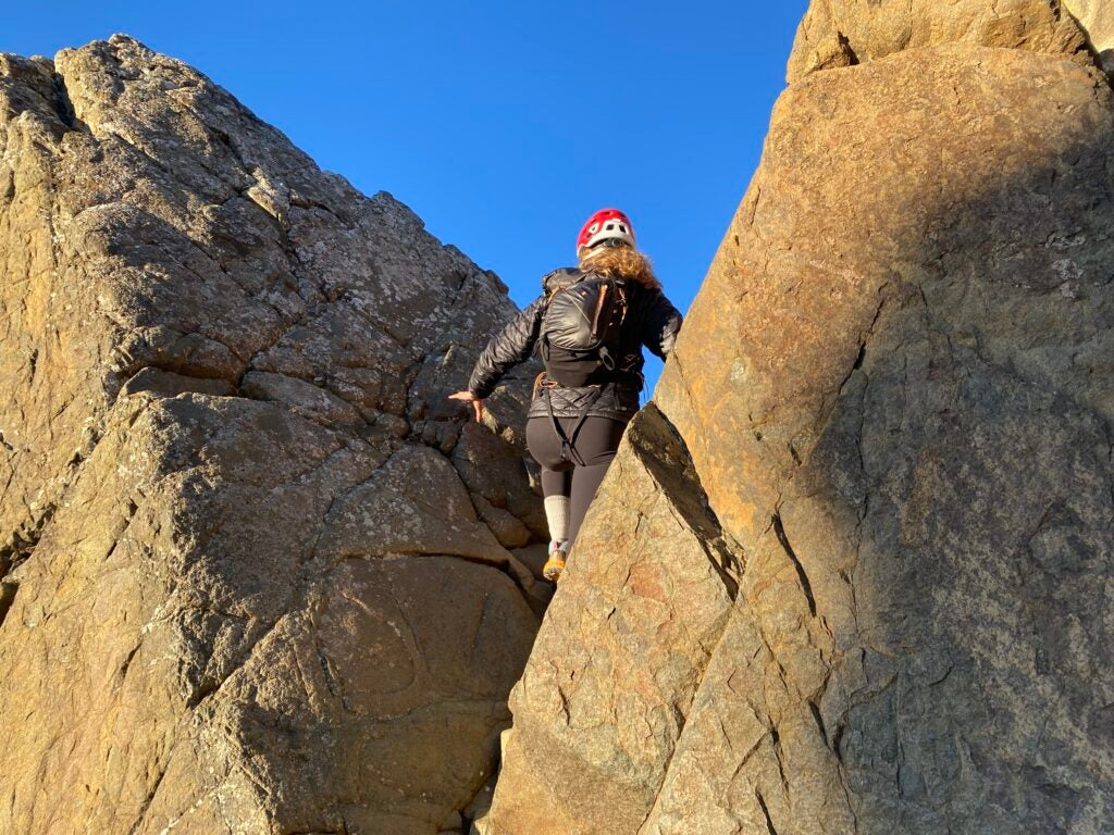 A woman with a red climbing helmet and black backpack climbing through two large rocks.