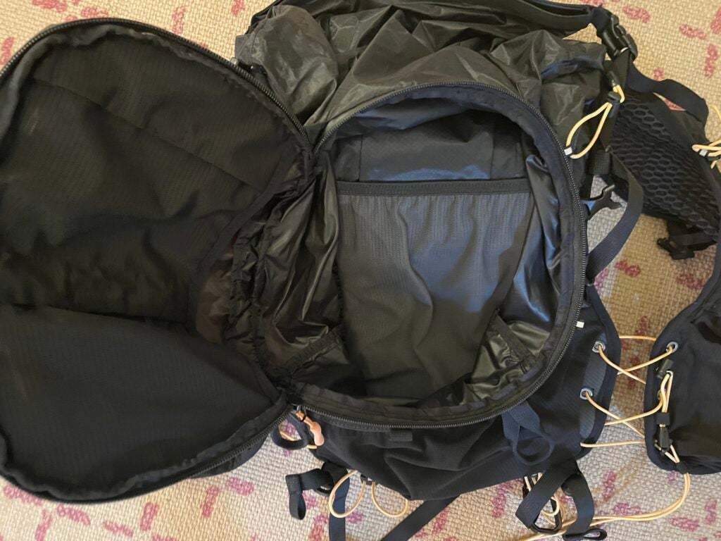 A black Deckers X Lab NVRSTP backpack with the front pocket open
