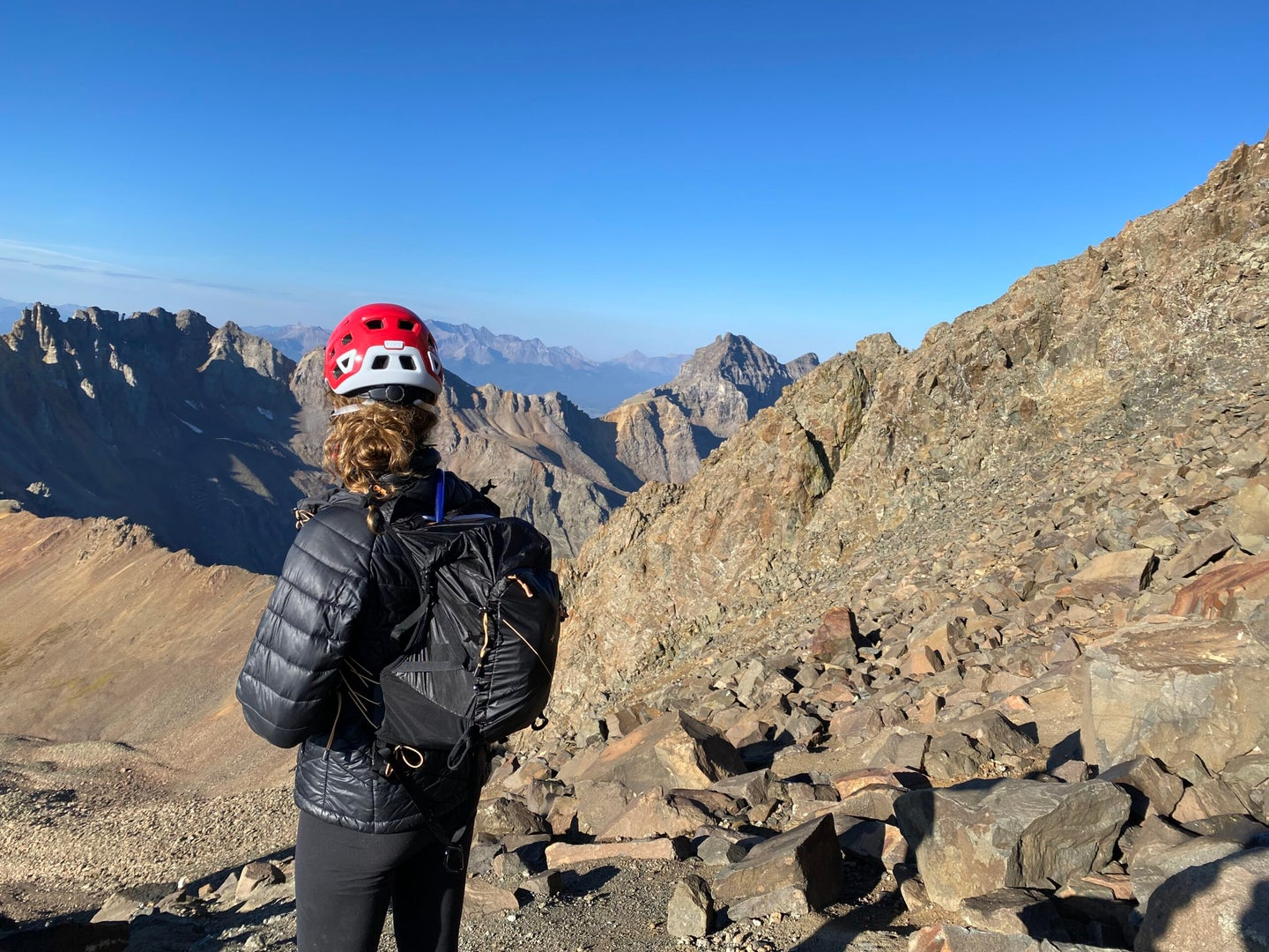 A woman with a black jacket, black backpack, and red climbing helmet looking over mountains