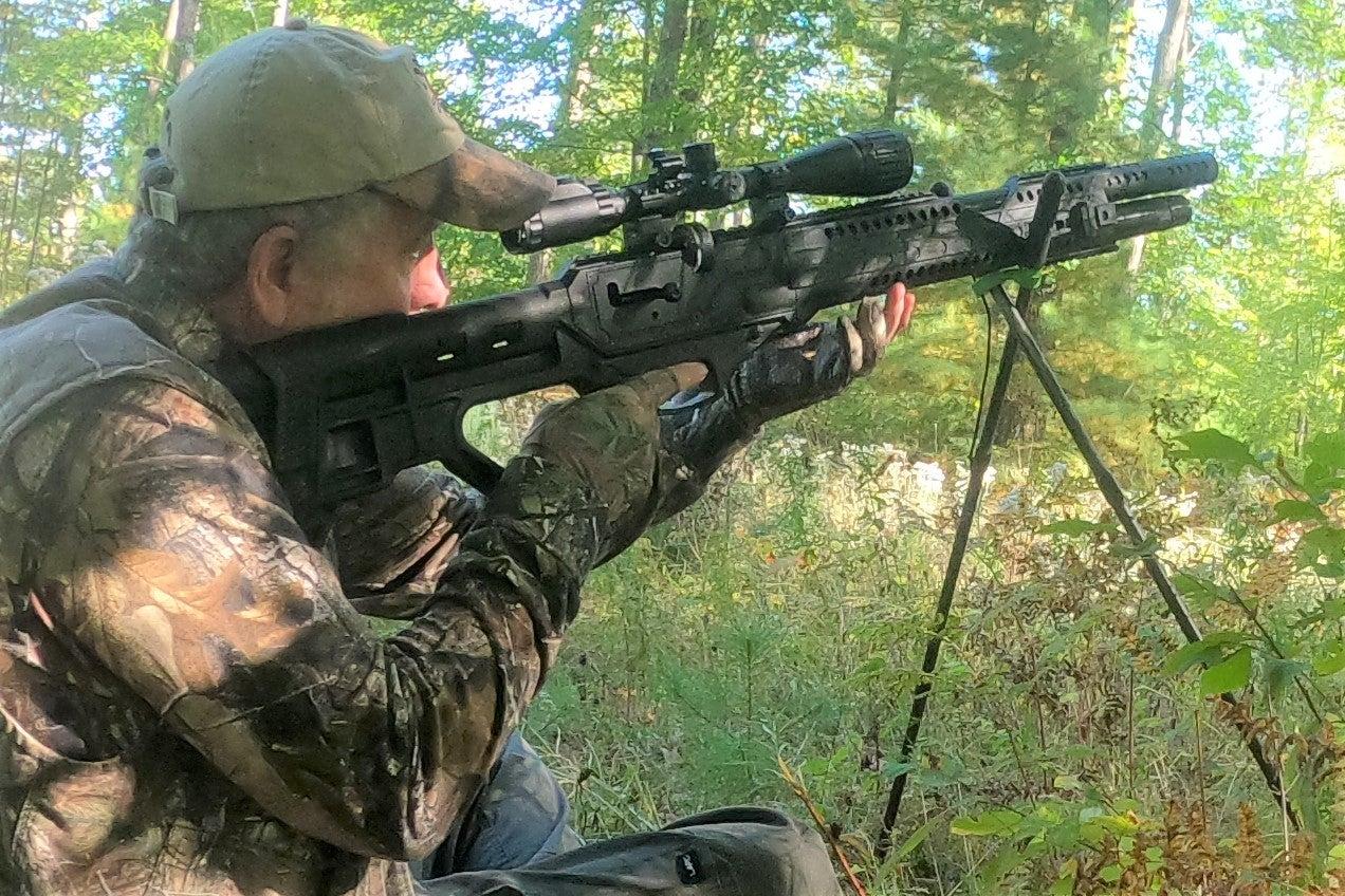 A man shooting a black air gun in the woods