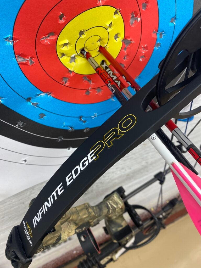 Three red arrows in the bullseye of a target with a Infinite Edge Pro behind them