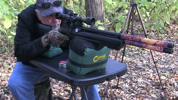 A man shooting an air rifle in the woods