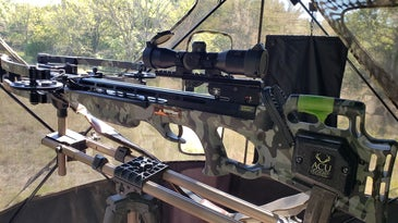 A black crossbow set up in a hunting blind