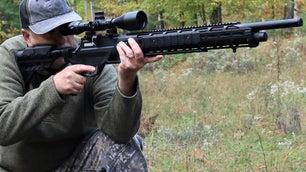 A man preparing to shoot a black air rifle