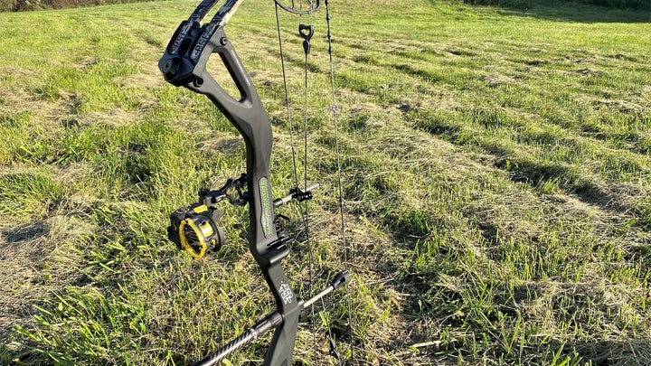 A green PSE Levitate bow standing up in a field